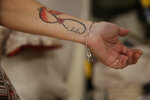 Debbi Hixon, shows a tattoo of a cardinal, the number fourteen, and the signature on  the last Valentines Day card that husband Chris Hixon wrote on the card before he died two years ago on Friday, Feb. 14, 2020, in Hollywood, Fla.  Her husband was gunned down at Marjory Stoneman Douglas High School along with 16 others in 2018. (AP Photo/Brynn Anderson)