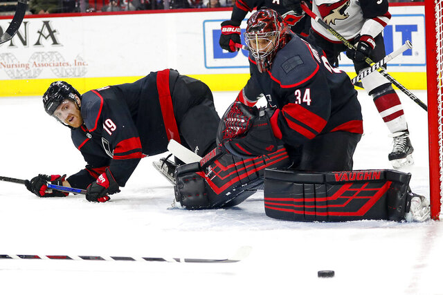 Carolina Hurricanes' Dougie Hamilton (19) and goaltender Petr Mrazek (34) eye the puck as it travels wide of the net during the first period of the team's NHL hockey game against the Arizona Coyotes in Raleigh, N.C., Friday, Jan. 10, 2020. (AP Photo/Karl B DeBlaker)