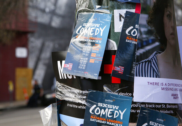 FILE - This March 12, 2016 file photo shows flyers advertising comedy on a light pole on Sixth Street during South By Southwest in Austin, Texas. Austin city officials have canceled the South by Southwest arts and technology festival. Mayor Steve Adler announced a local disaster as a precaution because of the threat of the novel coronavirus, effectively cancelling the annual event that had been scheduled for March 13-22. (Photo by Rich Fury/Invision/AP, File)