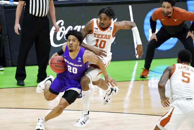 Abilene Christian's Coryon Mason (20) tries to get past Texas' Donovan Williams (10) during the first half of a college basketball game in the first round of the NCAA tournament at Lucas Oil Stadium in Indianapolis Saturday, March 20, 2021. (AP Photo/Mark Humphrey)