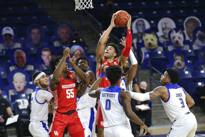 CORRECTS SPELLING TO QUENTIN, INSTEAD OF QUENTON - Houston's Quentin Grimes drives to the basket against Tulsa defenders, including Curtis Haywood III and Elijah Joiner, during the first half of an NCAA college basketball game in Tulsa, Okla., Tuesday, Dec. 29, 2020. Houston's Brison Gresham is at left. (AP Photo/Dave Crenshaw)