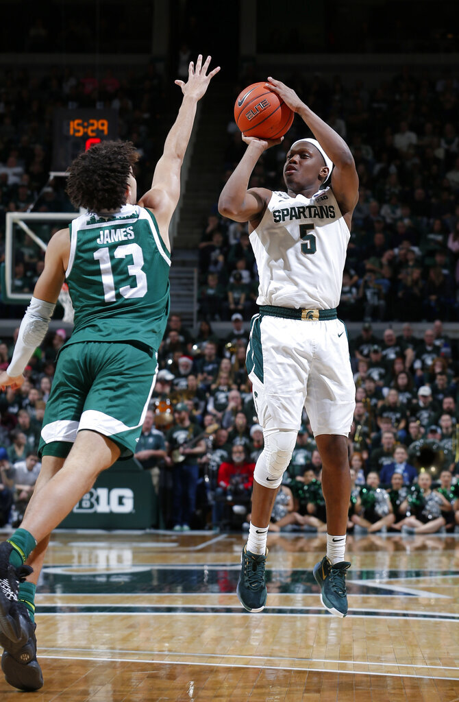 Michigan State's Cassius Winston, right, shoots against Eastern Michigan's Chris James (13) during the second half of an NCAA college basketball game, Saturday, Dec. 21, 2019, in East Lansing, Mich. (AP Photo/Al Goldis)