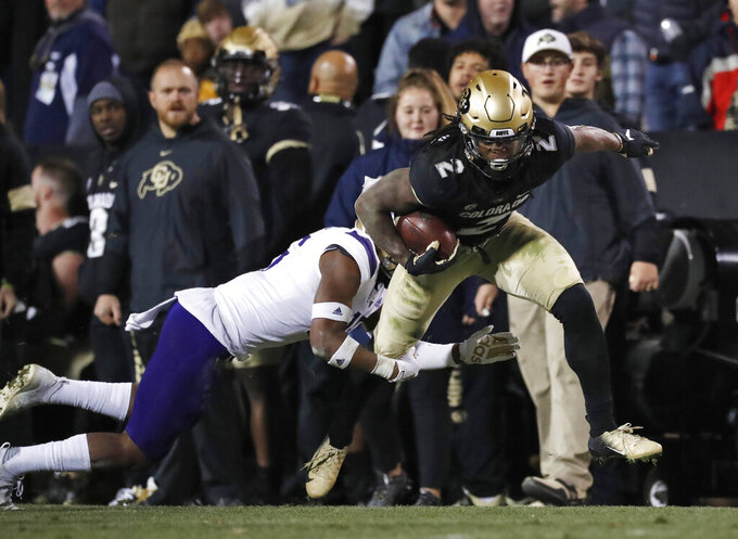 FILE - In this Nov. 23, 2019, file photo, Colorado wide receiver Laviska Shenault Jr., right, runs past Washington defensive back Cameron Williams after a pass reception during the second half of an NCAA college football game in Boulder, Colo. Shenault was selected by the Jacksonville Jaguars in the second round of the NFL football draft Friday, April 24, 2020. (AP Photo/David Zalubowski, File)