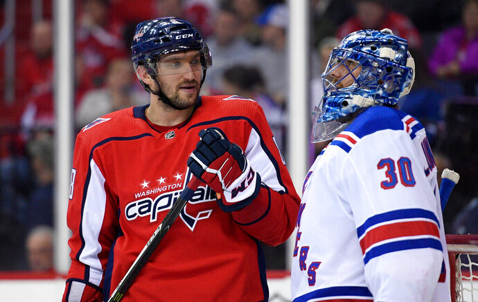 FILE - In this March 28, 2018, file photo, Washington Capitals left wing Alex Ovechkin (8), of Russia, with New York Rangers goaltender Henrik Lundqvist (30), of Sweden, during the second period of an NHL hockey game in Washington. Lundqvist signed with the Capitals when free agency opened Friday, Oct. 9, 2020. (AP Photo/Nick Wass, File)