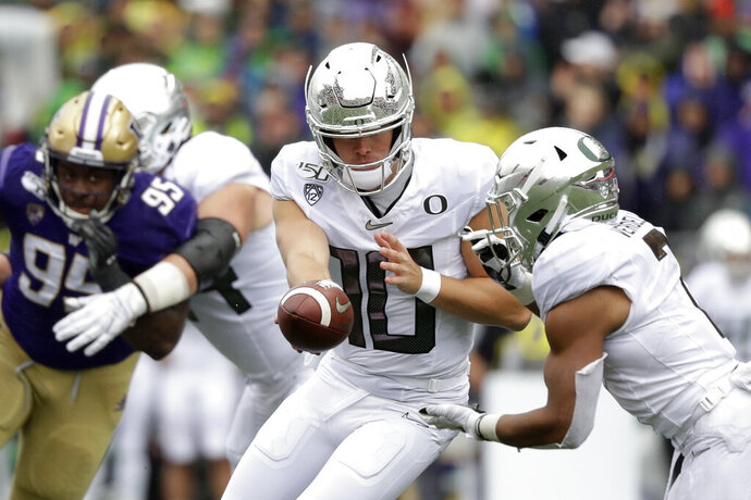 Oregon quarterback Justin Herbert (10) hands-off to CJ Verdell against Washington in the first half of an NCAA college football game Saturday, Oct. 19, 2019, in Seattle. (AP Photo/Elaine Thompson)