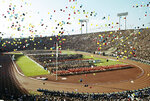 FILE - In this Oct. 10, 1964, file photo, balloons fly over Olympians and spectators during the opening ceremony of the 1964 Summer Olympics at the National Stadium in Tokyo. Every Japanese of a certain age has memories of the 1964 Tokyo Olympics. Even younger Japanese have connections through parents or aunts and uncles who saved old photos, faded certificates, or recall getting a television for the first time to watch the Games. (AP Photo, File)