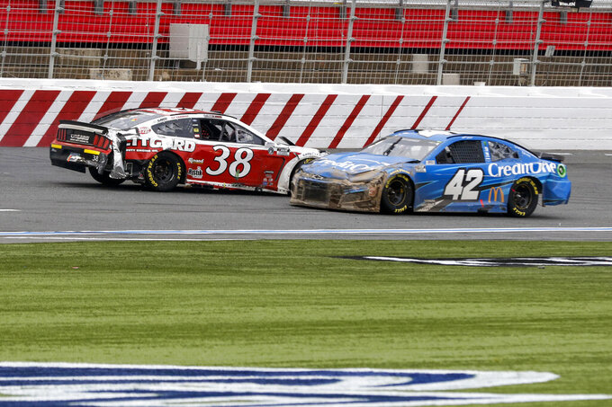 Matt Kenseth (42) drives past John Hunter Nemechek (38) after Nemechek spun out in a NASCAR Cup Series auto race at Charlotte Motor Speedway in Concord, N.C., Sunday, Oct. 11, 2020. (AP Photo/Nell Redmond)