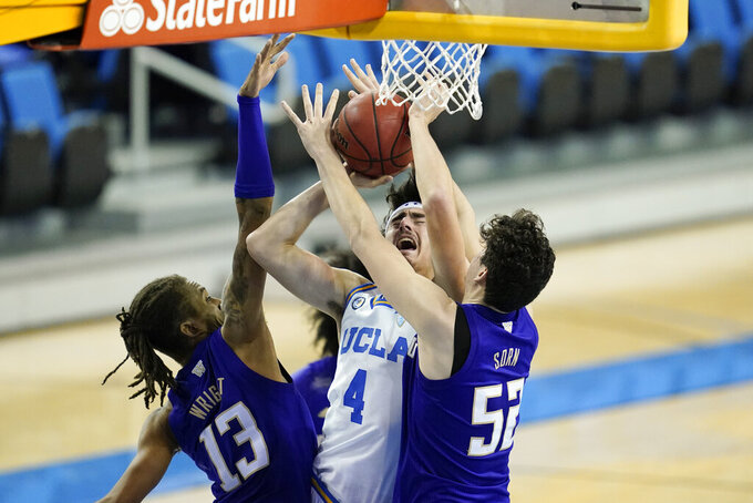 Washington forward Hameir Wright (13) and center Riley Sorn (52) break up a shot by UCLA guard Jaime Jaquez Jr. (4) during the second half of an NCAA college basketball game Saturday, Jan. 16, 2021, in Los Angeles. (AP Photo/Ashley Landis)