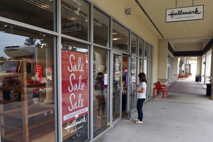 A sale sign is displayed near the entrance of a Hallmark store Tuesday, Jan. 12, 2021, in Orlando, Fla.  Retail sales fell for a third straight month, as a surge in virus cases kept people away from stores and restaurants during the holiday shopping season.     The report released Friday is yet another sign that the pandemic is slowing the U.S. economy. Last month, the country lost jobs for the first time since the spring.(AP Photo/John Raoux)