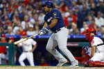 Milwaukee Brewers' Jesus Aguilar, left, watches his two-run single off Philadelphia Phillies starting pitcher Jake Arrieta during the third inning of a baseball game Wednesday, May 15, 2019, in Philadelphia. At right is Phillies catcher J.T. Realmuto. (AP Photo/Matt Slocum)
