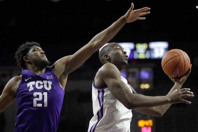 Kansas State forward Makol Mawien, right, drives past TCU center Kevin Samuel (21) during the second half of an NCAA college basketball game in Manhattan, Kan., Tuesday, Jan. 7, 2020. (AP Photo/Orlin Wagner)