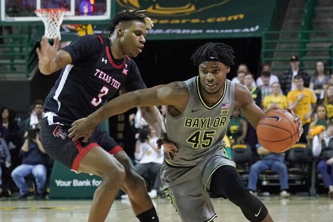 Baylor's Davion Mitchell (45) drives against Texas Tech's Jahmi'us Ramsey (3) during the first half of an NCAA college basketball game in Waco, Texas, Monday, March 2, 2020. (AP Photo/Chuck Burton)
