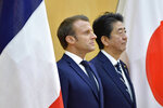 French President Emmanuel Macron, left, and Japanese Prime Minister Shinzo Abe review an honor guard prior to their meeting at Abe's official residence, Wednesday, June 26, 2019, in Tokyo. Macron will attend the G20 Osaka Summit which will be held on June 28th and 29th in Osaka. (David Mareuil/Pool Photo via AP)