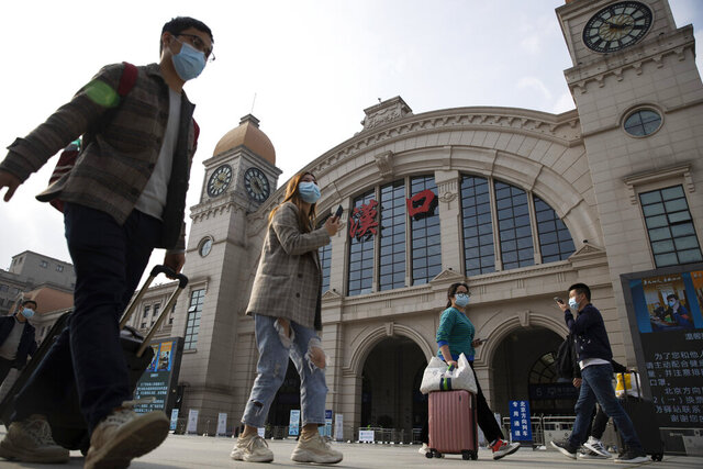 Travelers with their luggage walk past the Hankou railway station on the eve of its resuming outbound traffic in Wuhan in central China's Hubei province on Tuesday, April 7, 2020. Starting Wednesday, residents of Wuhan will be allowed to once again travel in and out of the sprawling city where the coronavirus pandemic began, ending an 11-week lockdown. (AP Photo/Ng Han Guan)