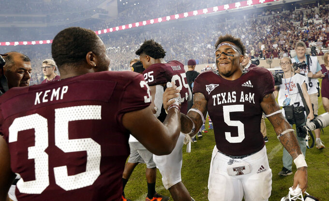 Texas A&M fullback Javonte Kemp (35) shakes hands with running back Trayveon Williams (5) at midfield after winning an NCAA college football game in overtime on Williams' score Saturday, Oct. 6, 2018, in College Station, Texas. (AP Photo/Michael Wyke)