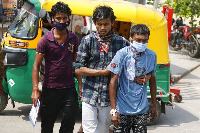 Relatives arrive with a COVID-19 patient at a dedicated COVID-19 government hospital in Ahmedabad, India, Tuesday, April 27, 2021. Coronavirus cases in India are surging faster than anywhere else in the world. (AP Photo/Ajit Solanki)
