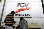 "A couple talks outside FGV Holdings Berhad, one of Malaysia's largest palm oil companies, in Kuala Lumpur, Thursday, Oct. 1, 2020. Malaysian palm oil producer FGV Holdings Berhad vowed Thursday to ""clear its name"" after the U.S. banned imports of its palm oil over allegations of forced labor and other abuses. (AP Photo/Vincent Thian)"