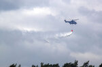 A helicopter drops water on a wildfire near Alt Jabel, Germany, Tuesday, July 2, 2019. Thousands of firefighters, soldiers and civil defense personnel are battling a large wildfire at an area used for military exercises in northern Germany. Officials said Tuesday that the blaze in Luebtheen, about 170 kilometers (106 miles) northwest of Berlin, is the biggest in the history of Mecklenburg Western Pomerania state. (Jens Buettner/dpa via AP)