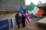 Two people hold EU, Ireland and Union Flags as they wait for the arrival of UK Brexit secretary Stephen Barclay to meet European Union chief Brexit negotiator Michel Barnier at the European Commission headquarters in Brussels, Friday, Oct. 11, 2019. (AP Photo/Francisco Seco)