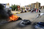 Sudanese protesters carry national flags and burn tyres during a demonstration to commemorate the first anniversary of a deadly crackdown carried out by security forces on protesters during a sit-in outside the army headquarters, in Khartoum, Sudan, Saturday, May 23, 2020. (AP Photo/ Marwan Ali)