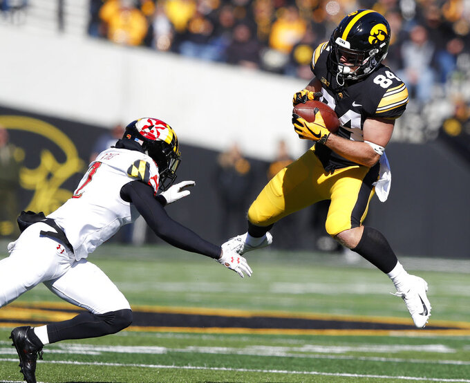 Iowa wide receiver Nick Easley (84) catches a pass in front of Maryland defensive back RaVon Davis, left, during the first half of an NCAA college football game, Saturday, Oct. 20, 2018, in Iowa City, Iowa. (AP Photo/Charlie Neibergall)