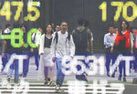 People are reflected on the electronic board of a securities firm in Tokyo, Tuesday, July 2, 2019. Most Asian stock markets have risen after Wall Street's benchmark hit a new high following the latest U.S.-Chinese trade truce. (AP Photo/Koji Sasahara)