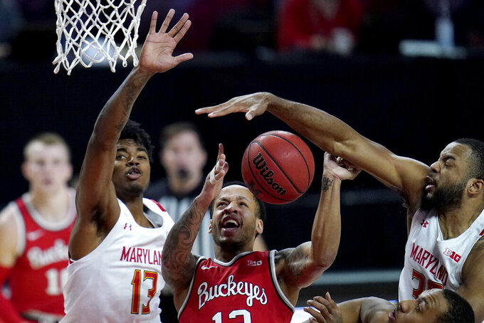 Ohio State guard CJ Walker, center, loses the ball while going up for a shot against Maryland guard Hakim Hart, left, and forward Galin Smith during the first half of an NCAA college basketball game, Monday, Feb. 8, 2021, in College Park, Md. (AP Photo/Julio Cortez)