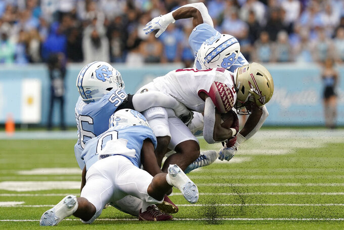 North Carolina defensive back Kyler McMichael, top, defensive lineman Tomari Fox (56) and defensive back Ja'Qurious Conley (0) tackle Florida State running back Jashaun Corbin during the second half of an NCAA college football game in Chapel Hill, N.C., Saturday, Oct. 9, 2021. (AP Photo/Gerry Broome)