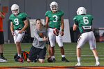 FILE - In this Tuesday, Aug. 6, 2019, file photo, Oklahoma State's Sean Gleeson, center, offensive coordinator/quarterbacks coach, runs a drill with quarterback Dru Brown (6) as quarterbacks Brendan Costello (9) and Spencer Sanders (3) look on during the NCAA college football team's practice in Stillwater Okla. Gleeson, the new offensive coordinator, was offensive coordinator for a Princeton squad that went undefeated in 2018. (AP Photo/Sue Ogrocki, File)
