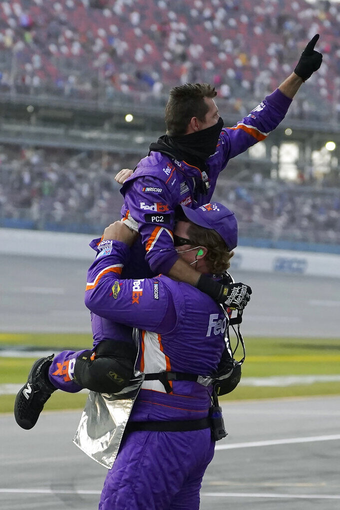 Members of Denny Hamlin's pit crew celebrate his win in the NASCAR Cup Series auto race at Talladega Superspeedway on Sunday, Oct. 4, 2020, in Talladega, Ala. (AP Photo/John Bazemore)