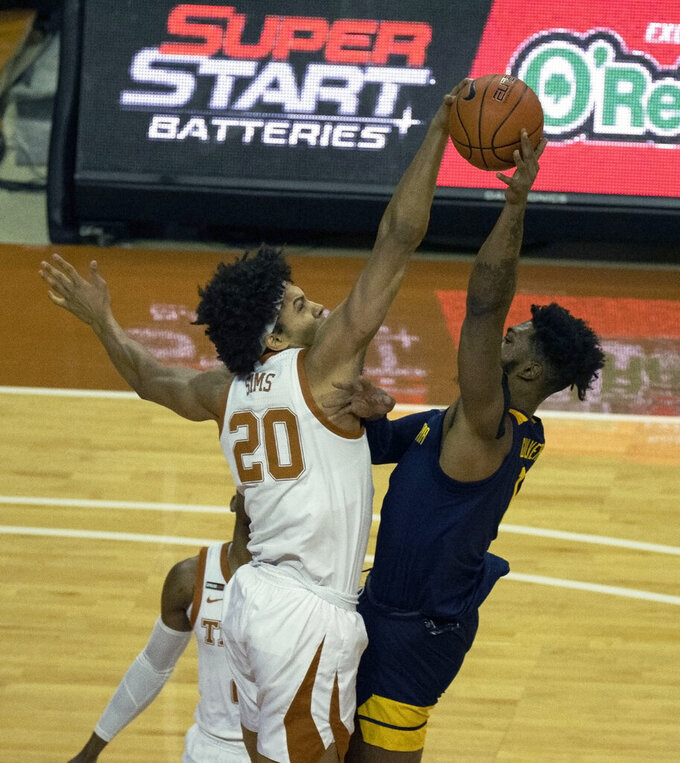Texas forward Jericho Sims, left, blocks the shot of West Virginia forward Derek Culver, right, during the first half of an NCAA college basketball game, Saturday, Feb. 20, 2021, in Austin, Texas. (AP Photo/Michael Thomas)