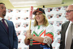 First baseman and member of the National Women's Baseball Team, Diamilette Quiles Alicea, center, is presented as the first female player to sign with The Utuado Highlanders, one of the teams that participate in the Superior Double A Baseball League, in San Juan, Puerto Rico, Thursday, May 16, 2019. Quiles Alicea shows the team's colors accompanied by the representative of the Montaneses of Utuado Rafael Juarbe, left, and the president of the Federation, Dr. Jose Quiles Rosas. (AP Photo/Carlos Giusti)