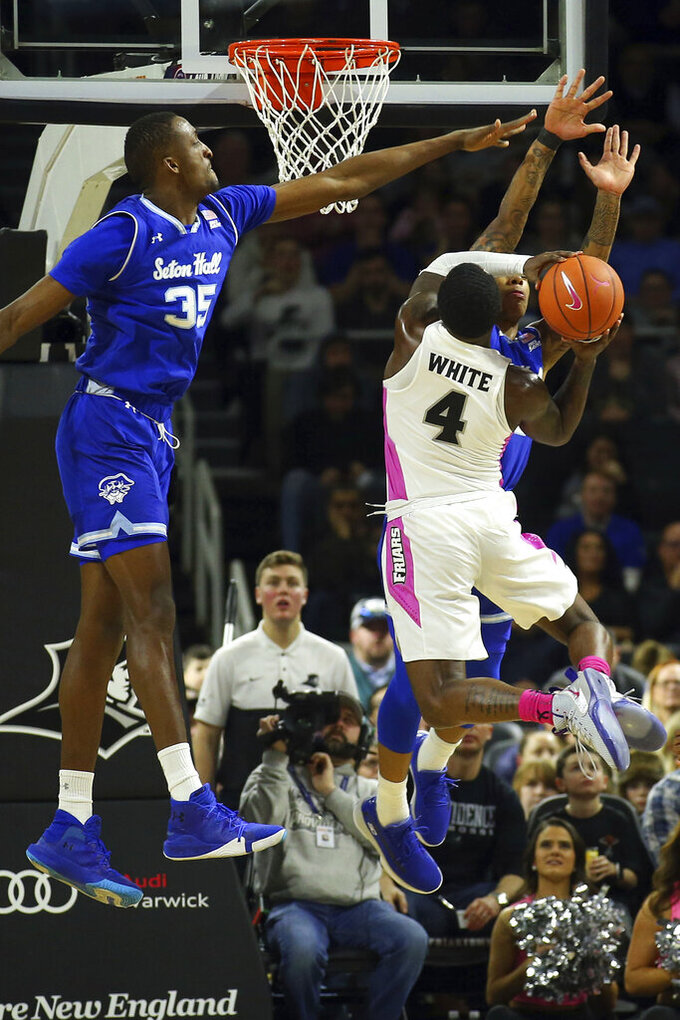 Seton Hall's Romaro Gill (35) and Shavar Reynolds, Jr., back right, attempt to block a shot by Providence's Maliek White (4) during the first half of an NCAA college basketball game Saturday, Feb. 15, 2020, in Providence, R.I. (AP Photo/Stew Milne)
