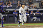New York Yankees' Aaron Judge watches his two-run home run during the third inning of the team's baseball game against the Texas Rangers, Wednesday, Sept. 4, 2019, in New York. Rangers catcher Jeff Mathis is at left. (AP Photo/Kathy Willens)