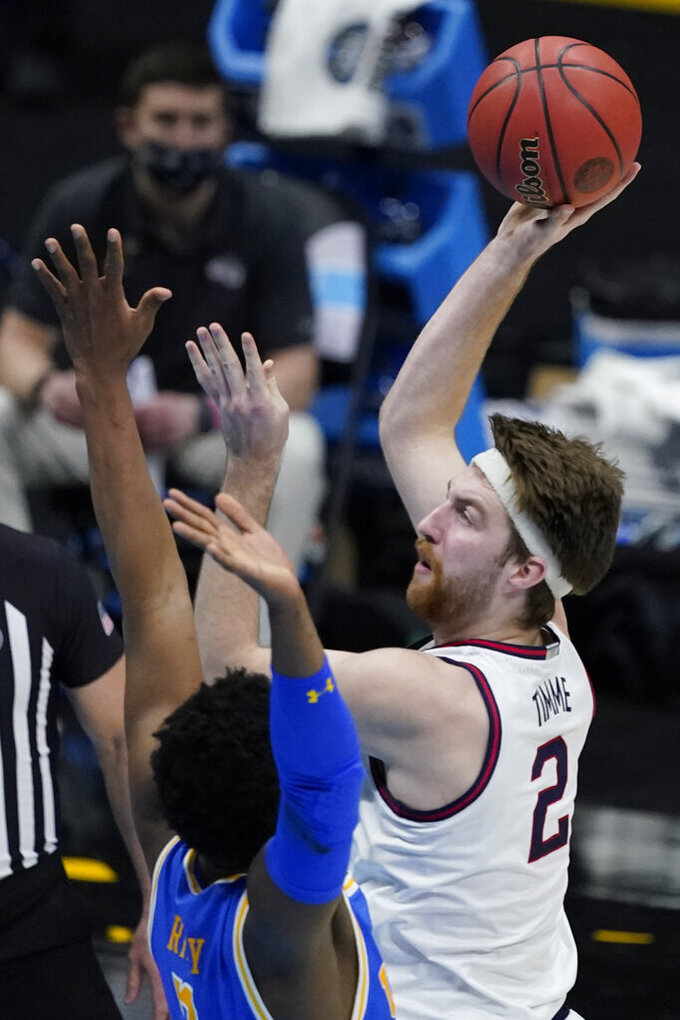 Gonzaga forward Drew Timme (2) shoots over UCLA forward Cody Riley, left, during the second half of a men's Final Four NCAA college basketball tournament semifinal game, Saturday, April 3, 2021, at Lucas Oil Stadium in Indianapolis. (AP Photo/Darron Cummings)