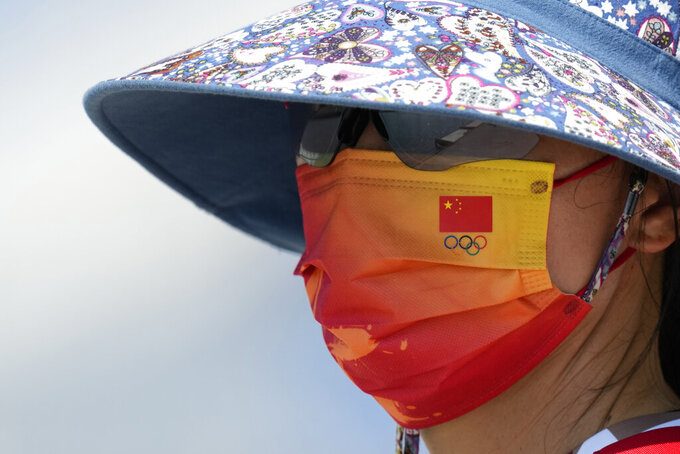 Chinese national flag and the Olympic rings are seen on the mask of a member of Chinese rowing team during a rowing training session at the 2020 Summer Olympics, Thursday, July 22, 2021, in Tokyo, Japan. (AP Photo/Lee Jin-man)