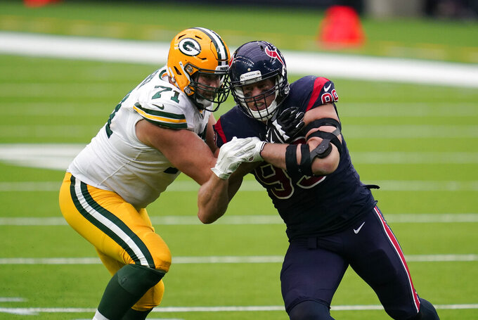 FILE - In this Sunday Oct. 25, 2020 file photo, Houston Texans defensive end J.J. Watt, right, rushes up field around Green Bay Packers offensive tackle Rick Wagner (71) during the second half of an NFL football game in Houston. The Green Bay Packers have released linebacker Christian Kirksey and offensive tackle Rick Wagner, two of their main veteran free-agent additions from a year ago.(AP Photo/Sam Craft, File)