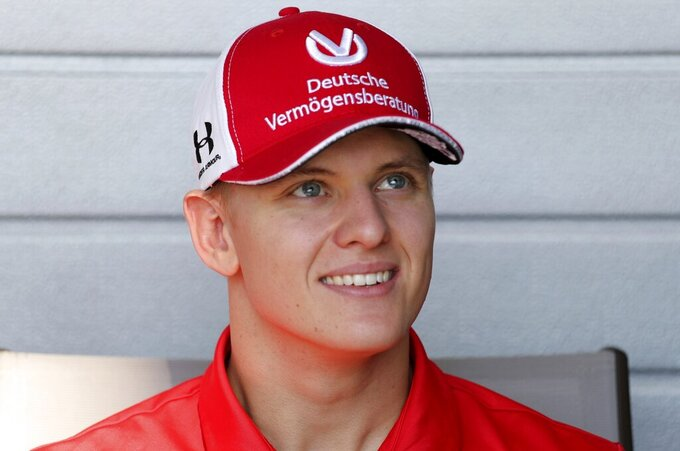 "FILE - In this Thursday, Nov. 28, 2019 file photo, German Formula Two driver Mick Schumacher talks to the journalists at the Yas Marina racetrack in Abu Dhabi, United Arab Emirates. Mick Schumacher celebrated his impending move into Formula One by clinching the F2 title on Sunday, Dec. 6, 2020. The 21-year-old German driver sounded emotional moments after crossing the line at the season-ending race in Bahrain.""I have no words,"" he said. ""Truly amazing."" (AP Photo/Kamran Jebreili file)"