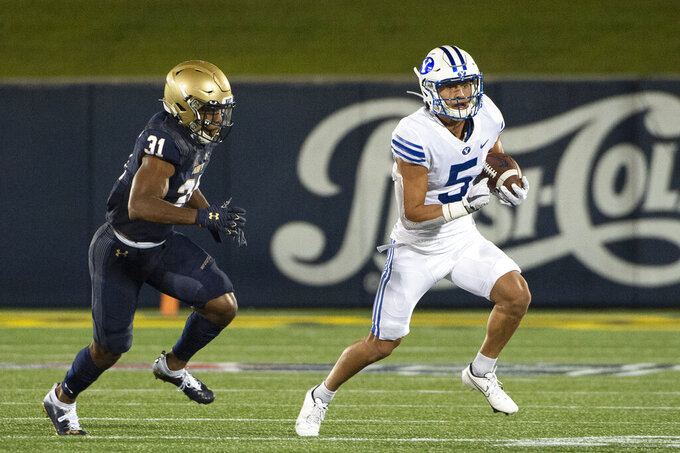 FILE - In this  Monday, Sept. 7, 2020 file photo, BYU's Dax Milne (5) runs after the catch as Navy linebacker Austin Talbert-Loving (31) defends during the first half of an NCAA college football game in Annapolis, Md. (AP Photo/Tommy Gilligan, File)