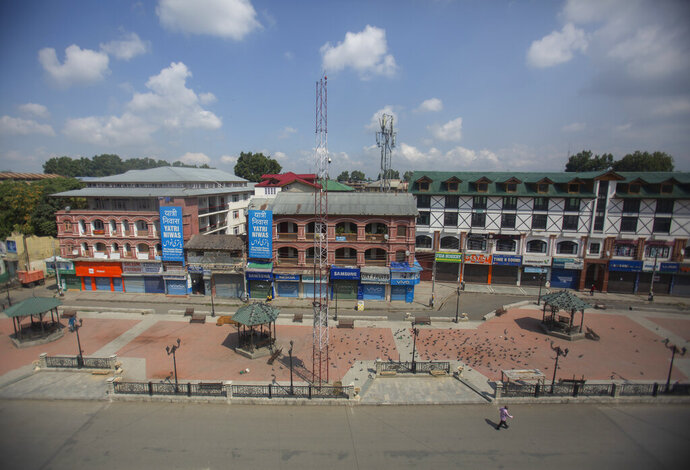 A man walks at a deserted market area during lockdown to stop the spread of the coronavirus in Srinagar, Indian controlled Kashmir,  July 22, 2020. Indian-controlled Kashmir's economy is yet to recover from a colossal loss a year after New Delhi scrapped the disputed region's autonomous status and divided it into two federally governed territories. (AP Photo/Mukhtar Khan)