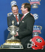 Georgia head coach Kirby Smart, right, and Texas head coach Tom Herman laugh during their photo opportunity with the Sugar Bowl trophy at a press conference on Monday, Dec 31, 2018, in New Orleans. No. 14 Texas will try to cap an impressive season when it faces No. 6 Georgia in the Sugar Bowl on Tuesday night, Jan. 1, 2019. (Curtis Compton/Atlanta Journal-Constitution via AP)