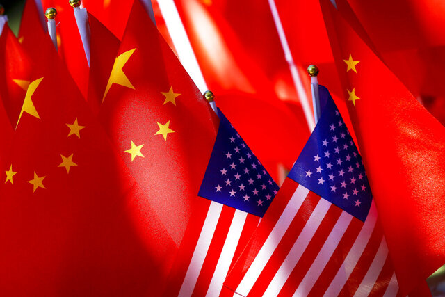 FILE - In this Sept. 16, 2018, file photo, American flags are displayed together with Chinese flags on top of a trishaw in Beijing. On Friday, Nov., 13, 2020, China has become one of the last major governments to congratulate Joe Biden on being elected U.S. president. (AP Photo/Andy Wong, File)