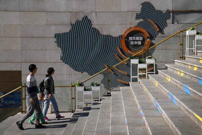 A family walks by a map showing Evergrande development projects in China at an Evergrande city plaza in Beijing, Tuesday, Sept. 21, 2021. Global investors are watching nervously as the Evergrande Group, one of China's biggest real estate developers, struggles to avoid defaulting on tens of billions of dollars of debt, fueling fears of possible wider shock waves for the Chinese financial system. (AP Photo/Andy Wong)