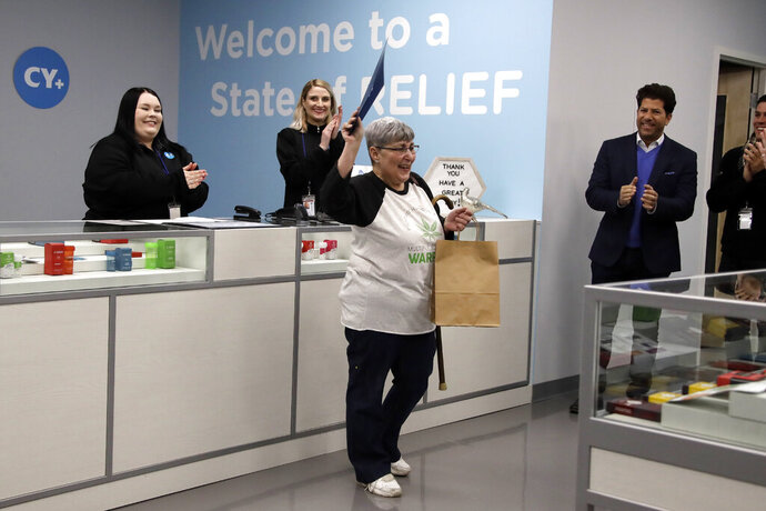 FILE - In this Jan. 16, 2019 file photo, Joan Caleodis, of Martin's Ferry, Ohio, center, celebrates being one of the first patient sales of Ohio's Medical Marijuana program at Cresco Labs CY+ dispensary in Winterville, Ohio.  A year after Caleodis became the first person in Ohio to purchase state-sanctioned medical marijuana, she said she remains mostly satisfied with the program but looks forward to a day when prices for cannabis products drop. Caleodis, 56, said she spends around $300 a month at local dispensaries to buy patches along with dried flowers, cannabis oil that she vapes to help treat primary progressive multiple sclerosis. (AP Photo/Gene J. Puskar)