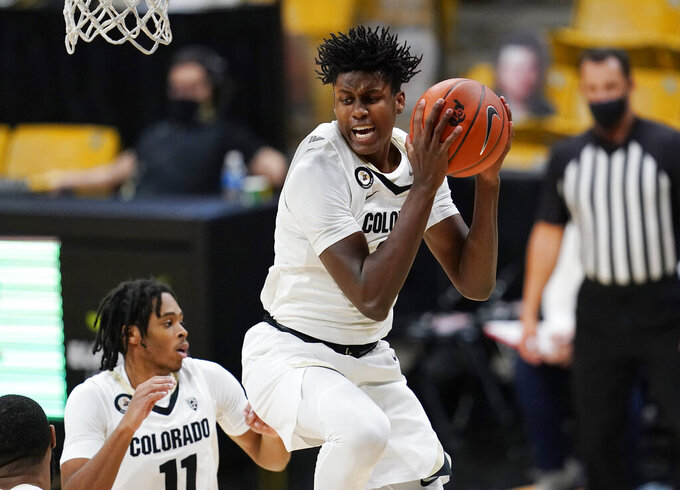 Colorado forward Jabari Walker pulls in a rebound as guard Keeshawn Barthelemy looks on in the second half of an NCAA college basketball game against Omaha Wednesday, Dec. 16, 2020, in Boulder, Colo. Colorado won 91-49. (AP Photo/David Zalubowski)