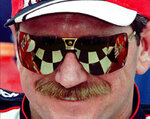 FILE - In this Feb. 13, 1997, file photo, the checkered flag  in Victory Lane reflects in the sunglasses of Dale Earnhardt,, after he won his eighth consecutive 125-mile qualifying auto race for the Daytona 500 at Daytona International Speedway in Daytona Beach, Fla. On the cusp of a national popularity explosion, NASCAR never stopped after the deaths of Adam Petty, Kenny Irwin Jr. and Tony Roper. But losing Earnhardt forced the stock car series to confront safety issues it had been slow to even acknowledge, let alone address. The dramatic upgrades have saved multiple lives — NASCAR has not suffered a racing death in its three national series since — and are the hallmark of Earnhardt's legacy. (AP Photo/Terry Renna, File)