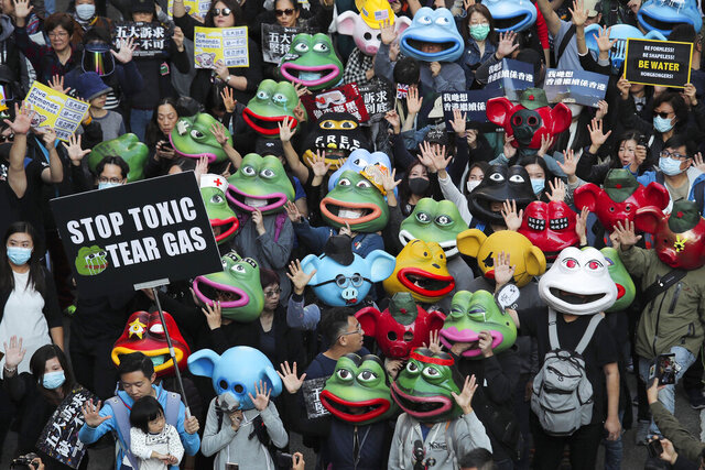 FILE - In this Dec. 8, 2019, file photo, pro-democracy protesters wear masks including those for Pepe the frog during a march in Hong Kong. Trump signs, Pepe the Frog graffiti and British, American and Hong Kong colonial-era flags have become common sights at Hong Kong protests, as the anti-government movement enters its eighth month. (AP Photo/Kin Cheung, File)