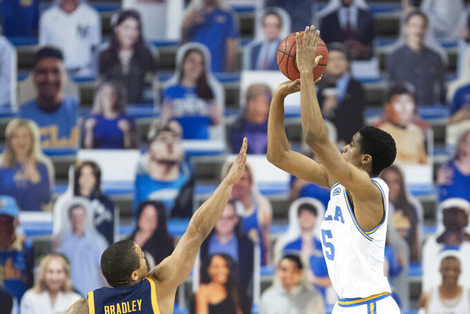 UCLA guard Chris Smith, right, shoots a three-point basket over California guard Matt Bradley during the first half of an NCAA college basketball game Sunday, Dec. 6, 2020, in Los Angeles. (AP Photo/Kyusung Gong)
