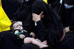 """A Lebanese Shiite supporter of Hezbollah listens to the story of Imam Hussein, during activities marking the holy day of Ashoura, in southern Beirut, Lebanon, Thursday, Aug. 19, 2021. The leader of the militant Hezbollah group Sayyed Hassan Nasrallah said Thursday that the first Iranian fuel tanker will sail toward Lebanon """"within hours"""" warning Israel and the United States not to intercept it. (AP Photo/ Hassan Ammar)"""