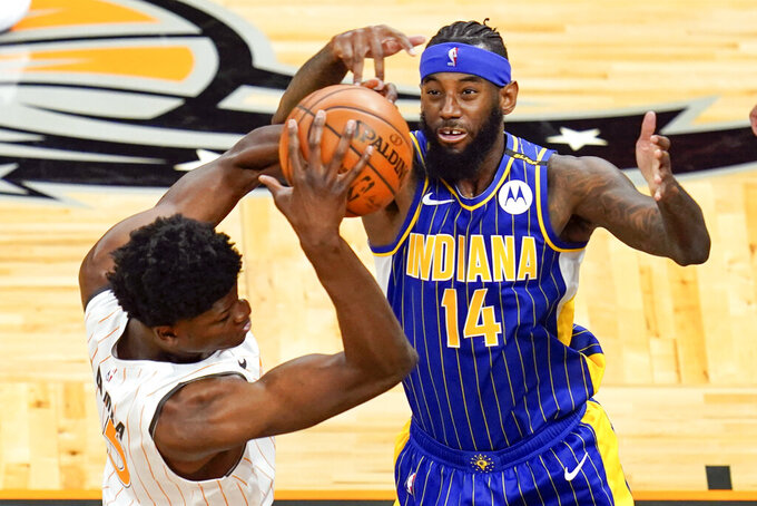 Orlando Magic center Mo Bamba, left, grabs a rebound away from Indiana Pacers forward JaKarr Sampson (14) during the first half of an NBA basketball game, Sunday, April 25, 2021, in Orlando, Fla. (AP Photo/John Raoux)